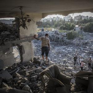 En palestinsk man tittar på sitt sönderbombade hur i Gaza.