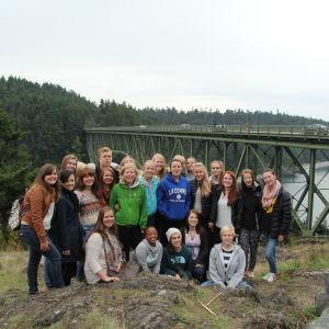 En grupp finländska elever och vänelever uppställda framför en bro i La Conner.