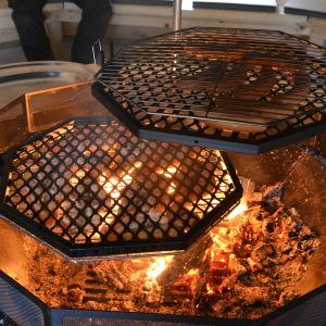 Lax och korv grillas över öppen eld i grillkåtan i Västerby friluftscentrum.