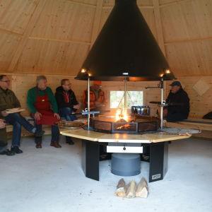 Folk värmer sig vid elden i den nya grillkåtan i Västerby friluftscentrum.