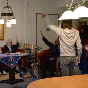 Närvårdarstuderande håller sittgymnastik för äldre på boendet Carl & Carolina i Vasa