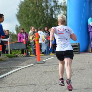 Anna Kultalahti kommer i mål vid Sun City Triathlon i Vasa, tränaren Mika Lehtonen hejar på.