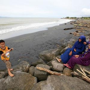 Indonesisk familj på stranden i Banda Aceh i Indonesien.
