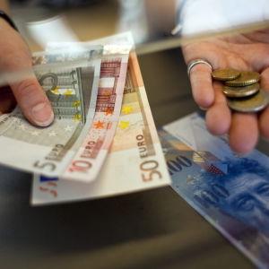 En kvinna växlar schweiziska frang till euro