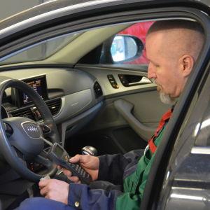 Bilmekanikern Kenth Österberg kontrollmäter bilavgaser innuti Audi