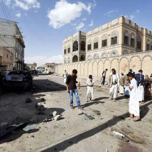 Människor inspekterar platsen i Sanaa där brutala självmordsattacker inträffade den 20 mars 2015.