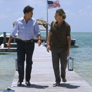 Två män går på en brygga med turkost vatten och en amerikaflagga i bakgrunden.
