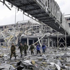 OSSE-observatörer och pro-ryska separatister vi den sönderbombade internationella flygplatsen i Donetsk.