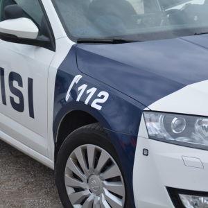 Polisbil med framdörren öppen.