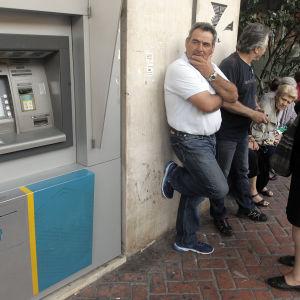 Greker har bildat en kö till en bankautomat i väntan på att automaterna ska börja fungera igen.