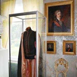 Kläderna på målningen bevarade i vitrinen. Stensböle gård.