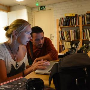 Katja Juhola och Fabio Cito sammanställer ett bildgalleri inför utställningen.
