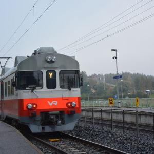 Y-tåg rullar in på en station, perrongen till vänster.