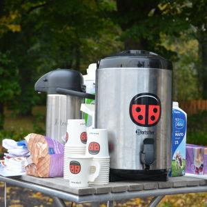 En stor kaffetermos och engångsmuggar med SFP-logo, mjölk och småbråd på ett litet trädgårdsbord, höstlöv i bakgrunden.