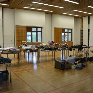 En stor gympasal, kläder och sängkläder r högar på många bord, skor på golvet, tomma papplådor