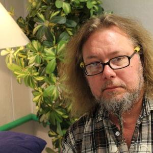 Pedro Viljanen istuu huonekasvin edessä