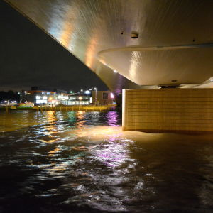 Underredet av bro och speglingar på vattenytan