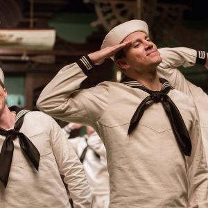 Musikaalielokuvassa tanssivat merimiehet vetävät kättä lippaan.