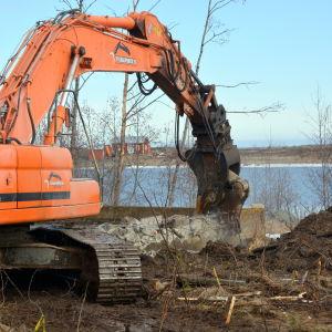 En grävmaskin river cementplattan som oljecisternerna har stått på.