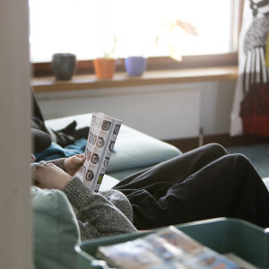 Barn sitter och läser i soffa