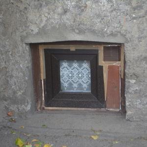 Ett trasigt fönster har dekorerats med vacker spetsduk.