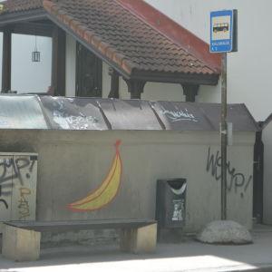 Busshållplats, någon har målat en stor banan på väggen bakom.