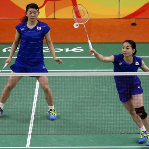 Ayaka Takahashi ser på när dubbelpartnern Misaki Matsumoto slår badmintonbollen över nätet.