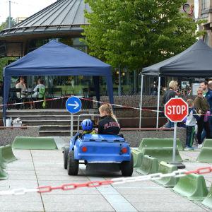 Barnens trafikdag i Vasa 2016. Fotat bakifrån när en instruktör sitter i en liten bil och ett barn kör bilen längs en bana.