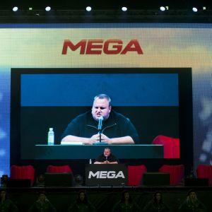 Kim Dotcom står i ett talarpodie med texten Mega. Han syns också på en stor skärm bakom podiet.