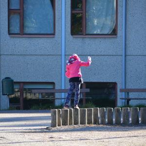 flicka balanserar på stolpar ute.