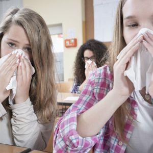 Två flickor snyter sig.