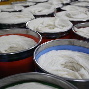 Runda metallcylindrar med rullar av återvunnet bomullsråmaterial i.