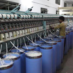 Bomullsslingor ur blåa cylindrar går in i en maskin som spinner tråd av dem.