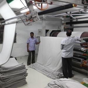 Färdigställning av bomullstyg, en bred länga med tyg kommer ut ur en maskin och viks på packe.