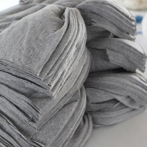 Hög med färdigklippta tygbitar som ska bli till t-skjortor.