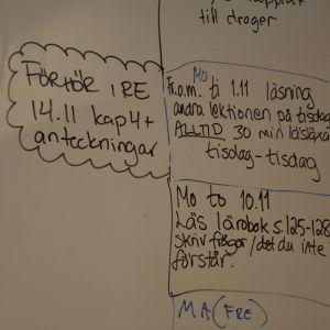 Anvisningar om läxor skrivna på tavla i skola.