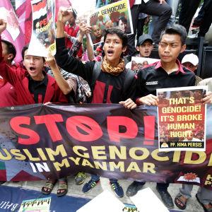 """Indonesiska aktivister håller upp en banderoll med texten: """"Stoppa folkmordet på muslimer"""" den 24.11.2016."""