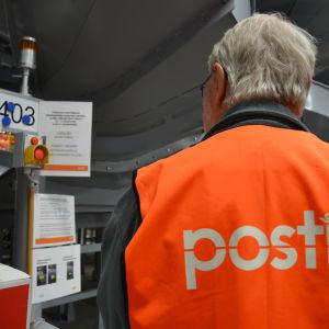 Postanställd på postcentralen i Lundo.