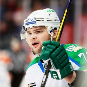 Grönklädd ishockeyspelare i profil följer med spelet från avbytarbänken.