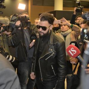Axl Smith anländer till rättssalen omgiven av kameror, mikrofoner och journalister.