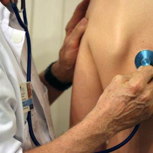 Läkare undersöker patient med stetostop.