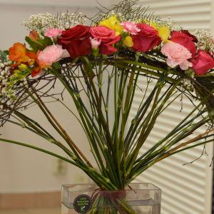 Blomsterarrangemang av rosor som ser ut som en solfjäder.