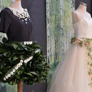 En brudklänning gjord av mörka gröna blad och små vita blommor.