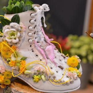 Vita höga skor med snörning som är dekorerade med gula blommor.