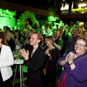 Glada människor applåderar på De grönas valvaka i Helsingfors.