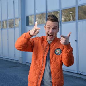 Programledaren Jontti Granbacka står på en parkering iklädd en orange jacka med logon för nya barnprogrammet Superhjälparna.