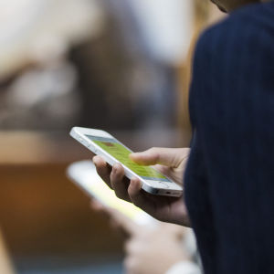 en person håller i en mobiltelefon