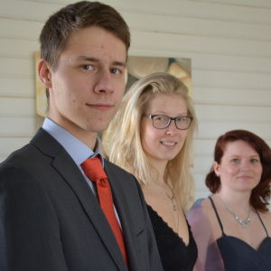 Ung man och två och unga kvinnor i festkläder.