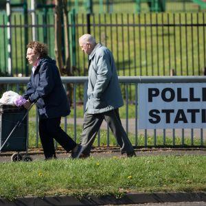 Ett äldre par passerar en vallokal i Manchester, norra England 4.5.2017