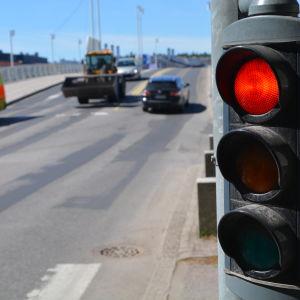 Rött trafikljus med trafik i bakgrunden